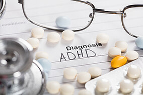 Glasses and tablets lying on a sheet of paper with the heading: Diagnosis ADHD.