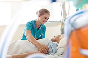 Krankenschwester kümmert sich um bettlägerige Patientin