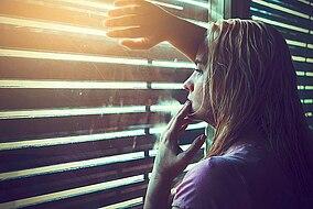 Frau lehnt an Fenster mit geschlossenem Rollladen