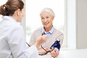 Ärztin misst den Blutdruck einer älteren Patientin