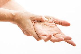 Mann hält seine schmerzende Hand