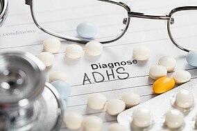 Brille und Tabletten auf einem Blatt Papier mit der Aufschrift Diagnose ADHS