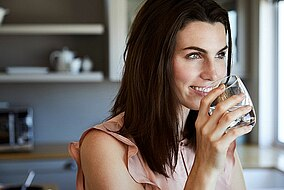 Frau mit einem Glas Wasser in der Hand