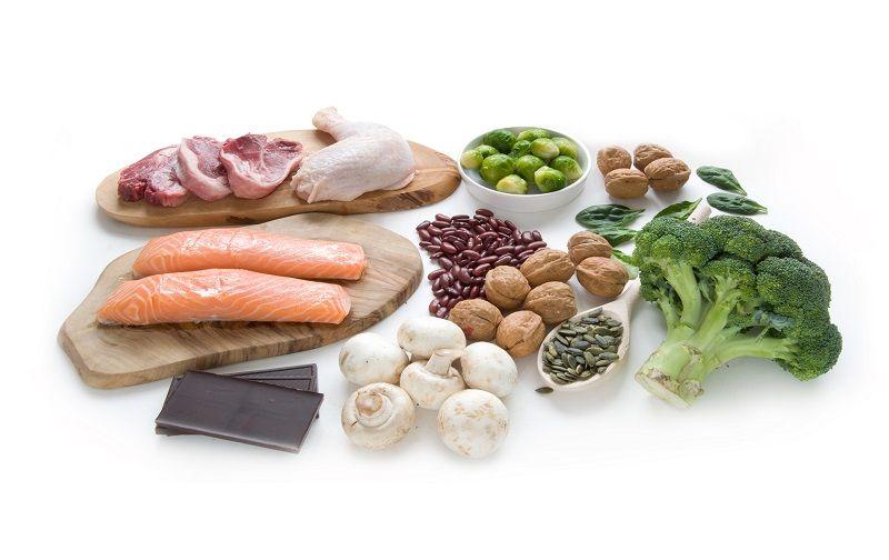 Verschiedene Fleischsorten, Lachs, Brokkoli, Nüsse, Rosenkohl, Champignons nebeneinander gelegt