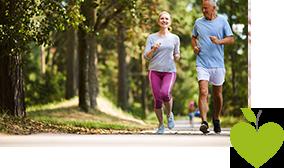 Eine Frau und ein Mann joggen gemeinsam durch den Wald