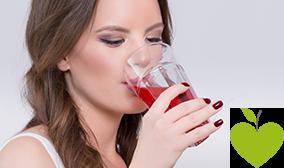 Junge Frau trinkt ein Glas Cranberrysaft