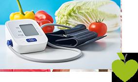 Blutdruckmessgerät mit Gemüse im Hintergrund