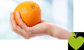 Frau hält eine Orange in der Hand