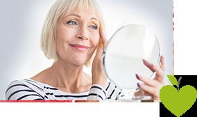 Ältere Frau schaut in einen Spiegel