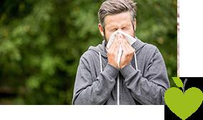 Mann steht in der Natur und hält sich ein Taschentuch vor die Nase
