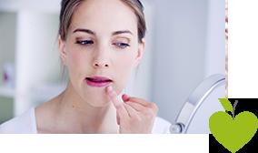 Frau schaut in einen Spiegel und untersucht ihren Lippenherpes
