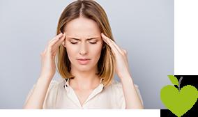 Frau hält sich den Kopf vor Schmerzen fest