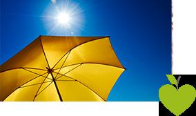 Ein gelber Sonnenschirm vor einem strahlend blauen Himmel mit Sonne