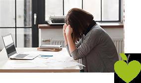 Frau sitzt am Schreibtisch vor einem Laptop und lässt den Kopf in die Hände fallen