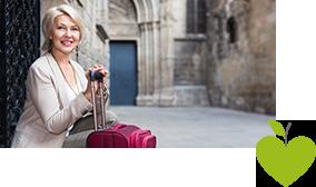 Frau sitzt mit einem Koffer vor einem alten Gebäude