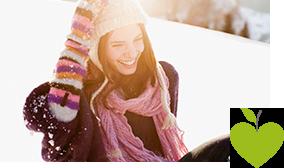 Junge Frau sitzt in sonniger Winterlandschaft