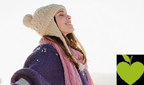 Junge Frau steht fröhlich in einer Winterlandschaft
