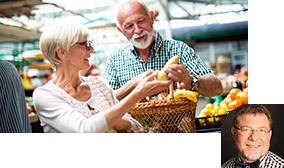 Ein Mann und eine Frau stehen an einem Obststand und halten eine Birne in der Hand