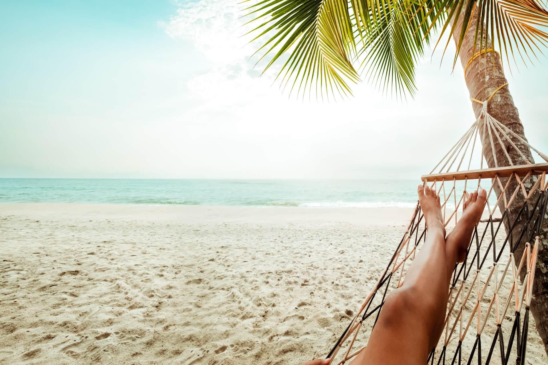 Vista dall amaca sotto le palme alla spiaggia e al mare: jakkapan21/iStock/Getty Images Plus